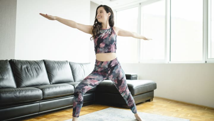 Young woman practicing yoga in front of a couch and bright sun-lit windows