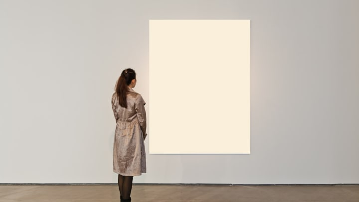 Woman looking at white frame in an art gallery