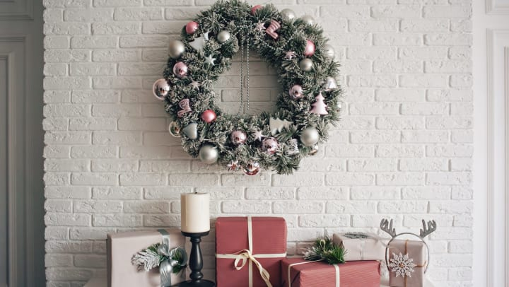 Festive table with holiday decorations and a wreath hanging above