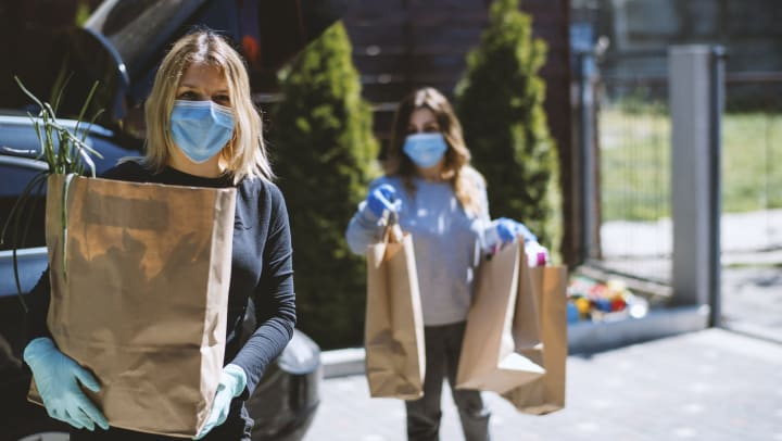 Two women wearing masks carrying groceries from a car, near The Slate