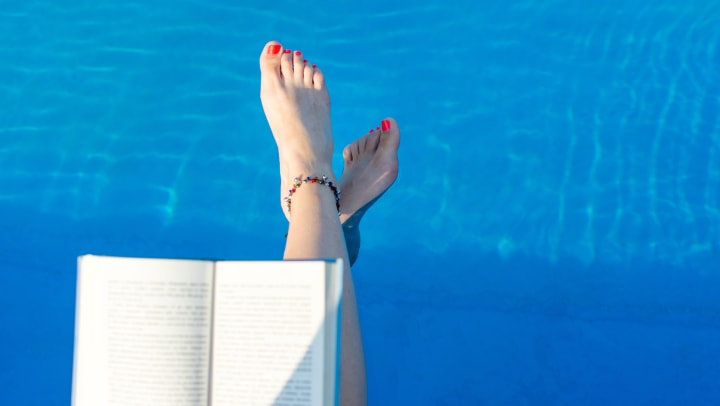 Resident reading a book poolside at Cactus Forty-2 in Phoenix, Arizona