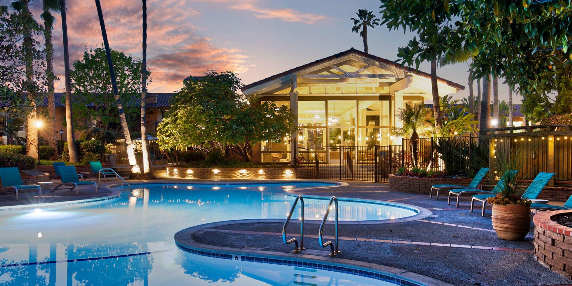 Underwater lights illuminating the swimming pool at twilight at Mediterranean Village Apartments in Costa Mesa, California