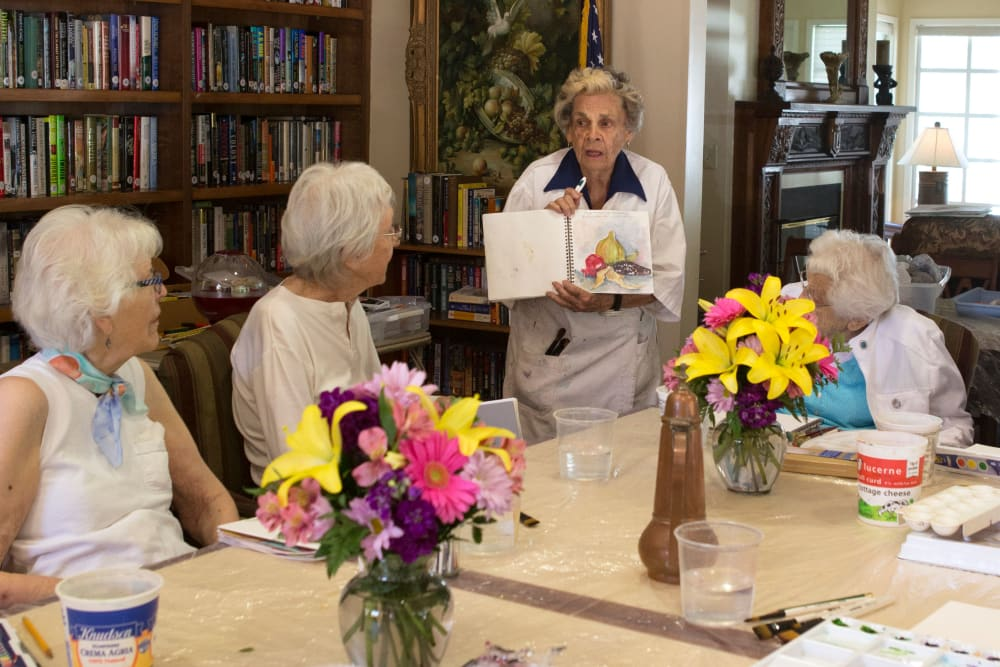 A resident showing other residents her artwork at Gables of Ojai in Ojai, California