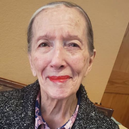 Resident sitting and smiling at Oxford Glen Memory Care at Sachse in Sachse, Texas