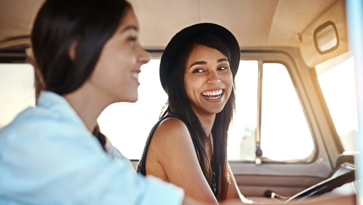 Resident friends smiling while driving on Route 66 near Olympus Solaire in Albuquerque, New Mexico