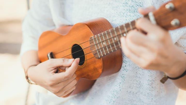 Woman playing a ukulele.