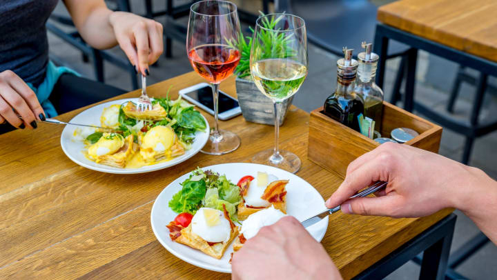Two plates of eggs benedict and two glasses of wine sitting on a wooden table