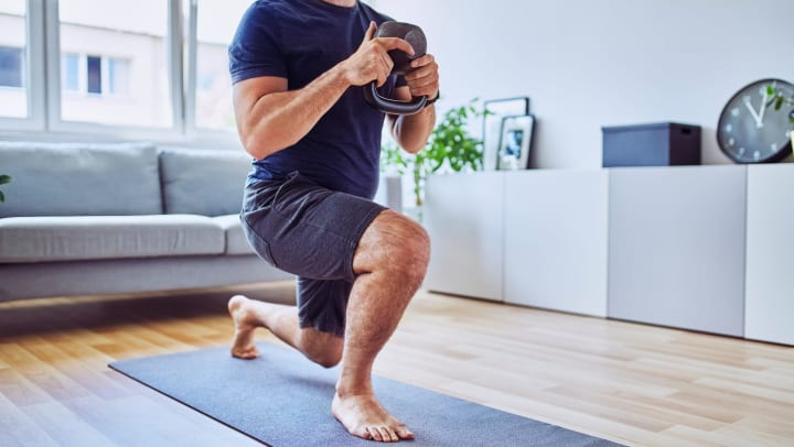 Man doing kettle bell workouts in his living room at his Olympus apartment