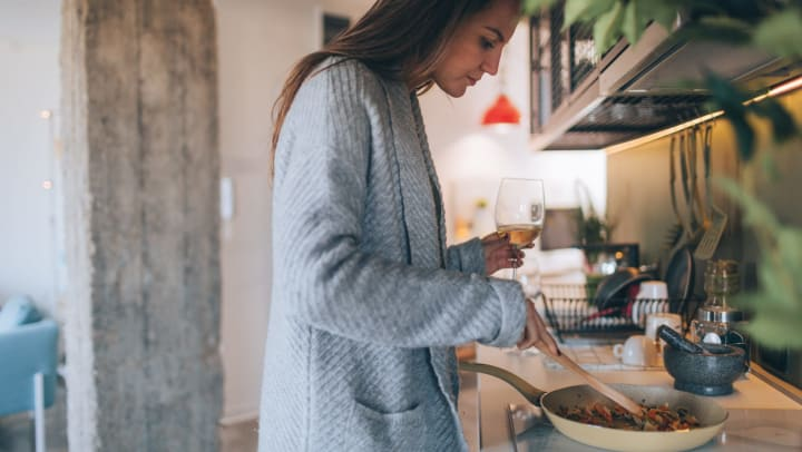 Woman cooks an easy dinner and drinks a glass of wine in her kitchen.