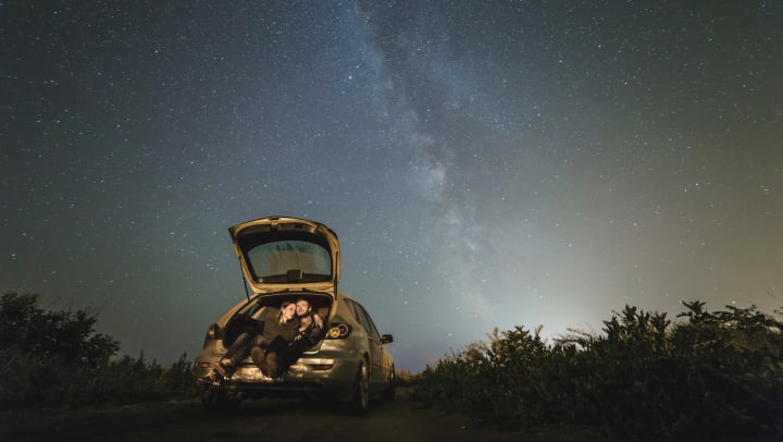 Couple sitting in the trunk of their car watching the stars at night near Canopy at Citrus Park