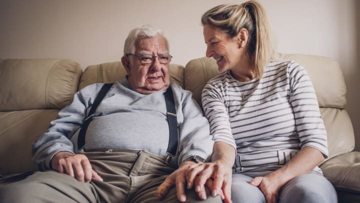 Woman sitting on the couch with her elderly father smiling at Senior Living Management property