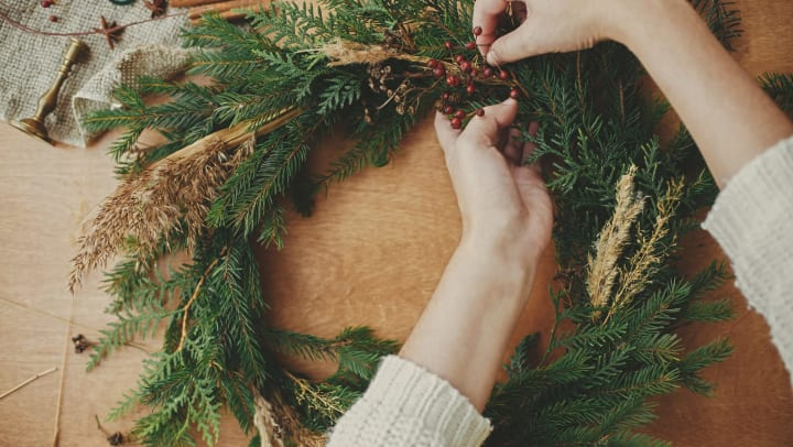 Person making a rustic Christmas wreath on the table
