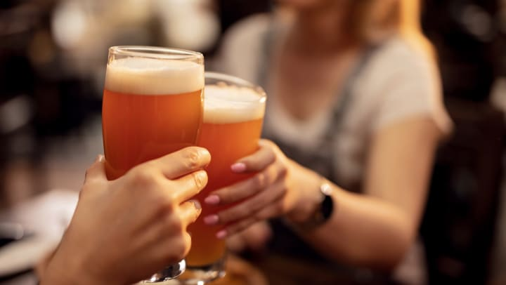 Close up of a couple toasting with lager beer.