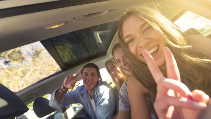 A group of young adults in the back of a car, smiling and giving peace signs with their hands.