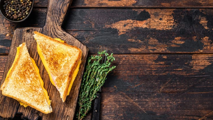 A grilled cheese sliced in half diagonally on a wooden cutting board with a bowl of peppercorns and a stick of rosemary next to it.
