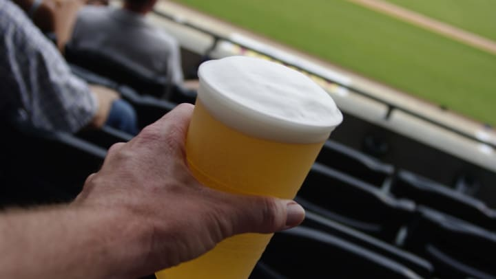 Closeup of man holding plastic cup of beer with baseball stadium blurred in background