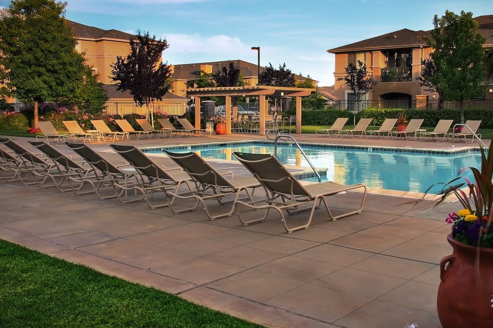 Spacious sundeck with table and chairs next to a swimming pool at Cross Pointe Apartment Homes in Antioch, California