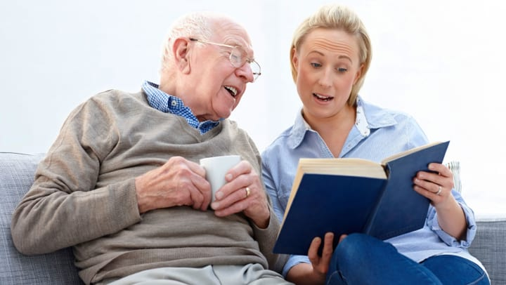 Female caregiver reading to a resident.