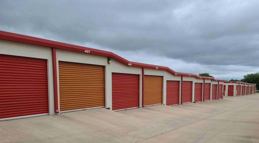 Exterior view of storage units with red and orange doors at KO Storage of Wichita Falls in Wichita Falls, Texas