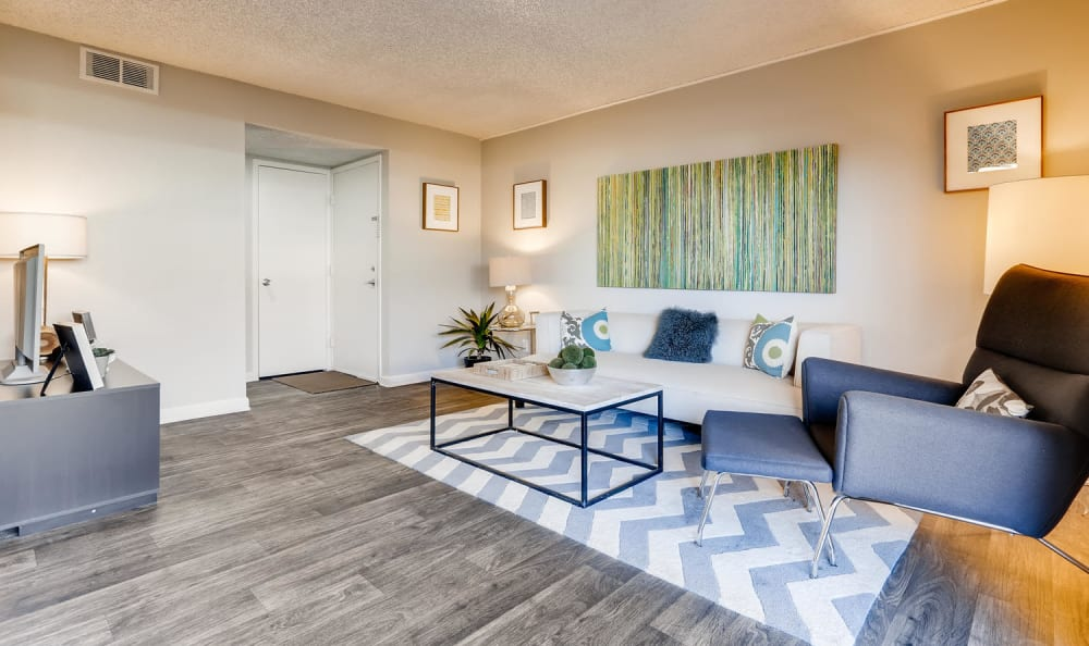 spacious modern living room with white couch blue chair coffee table and hardwood floors at The Ranch at Bear Creek Apartments & Townhomes in Lakewood, Colorado