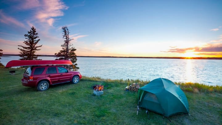A car with a kayak strapped atop it next to a campfire and a tent. A lake is in the background.