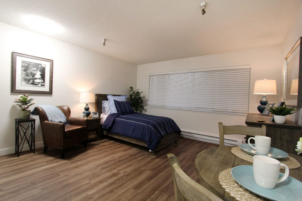 Bedroom with hardwood floors at The Village Senior Living in Tacoma, WA