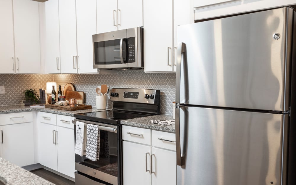 Granite countertops and a subway tile backsplash in model home's kitchen at Parc at Wesley Chapel in Wesley Chapel, Florida