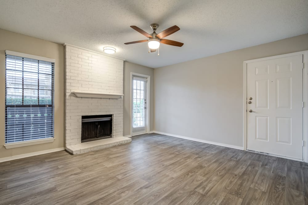 Hardwood floors and a fireplace in the open-concept floor plan of a model home at The Arbors of Carrollton in Carrollton, Texas