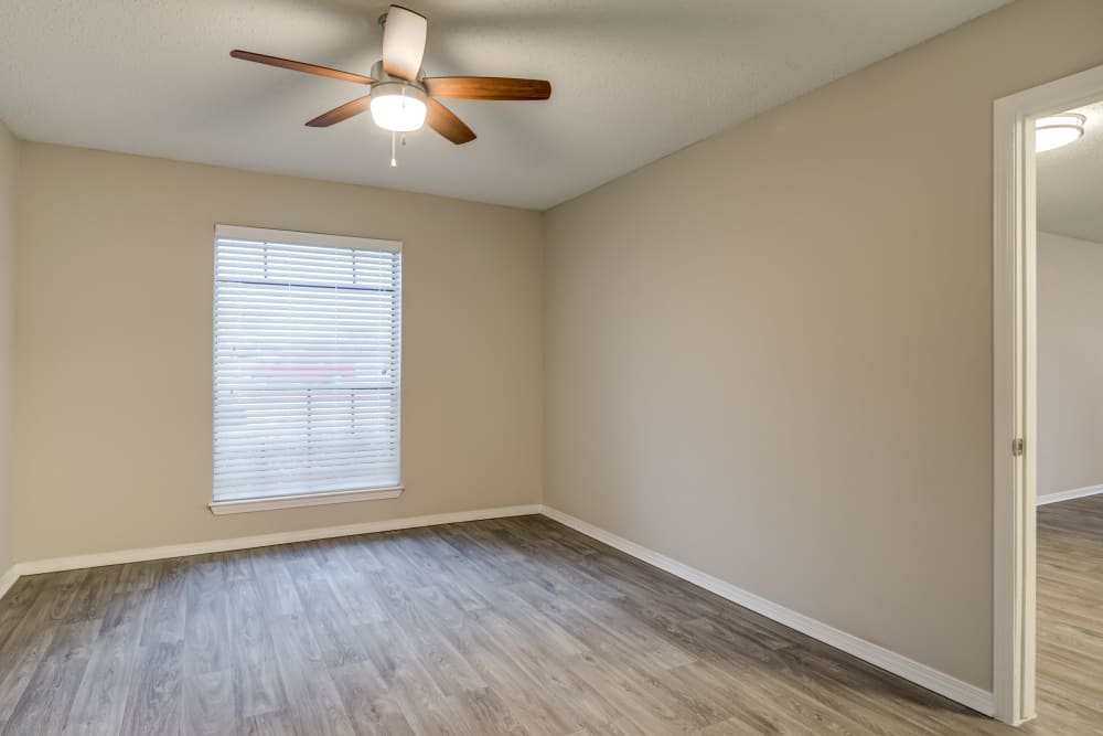 Ceiling fan and hardwood flooring in the living area of a model home at The Arbors of Carrollton in Carrollton, Texas