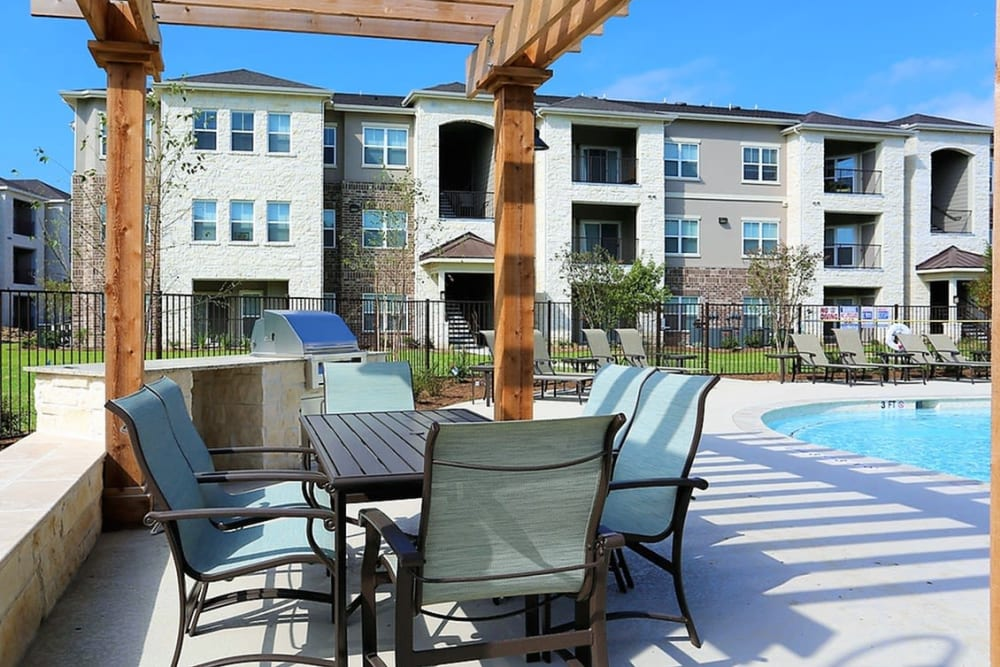 Poolside patio tables at Trails at Lake Houston in Houston, Texas