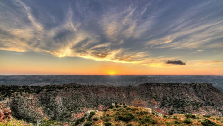 Landscape view of a sunrise over a vast red rock canyon with green shrubs
