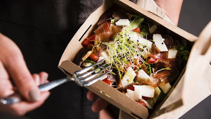 Person eats salad out of a takeout box.