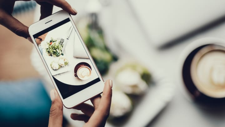 A woman holding a cellphone while taking a shot of her food from directly above.