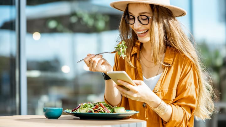 A smiling woman sitting at an outdoor table eats a salad as she looks at her phone.