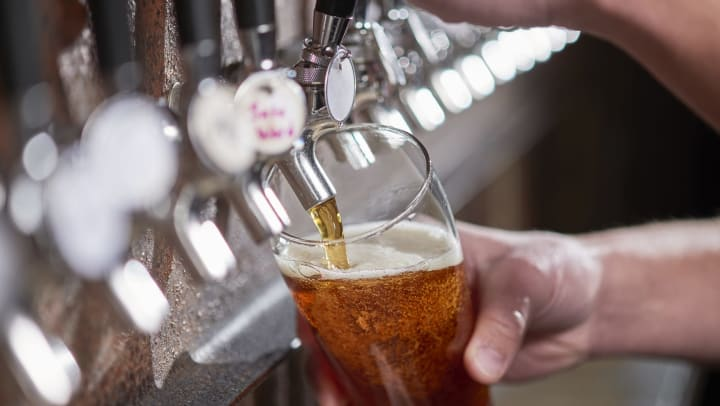 Person pouring a beer from a tap