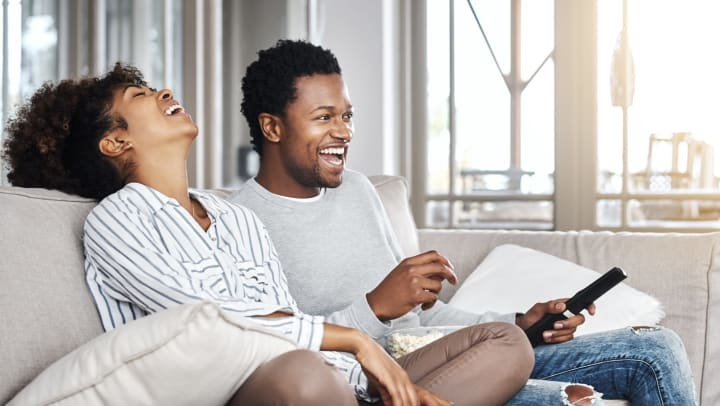Young man and young woman sitting on a couch in a sunlit interior and laughing while watching television