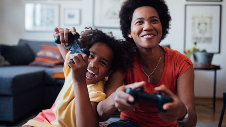 A laughing mother and daughter hold controllers as they play videogames in their living room.