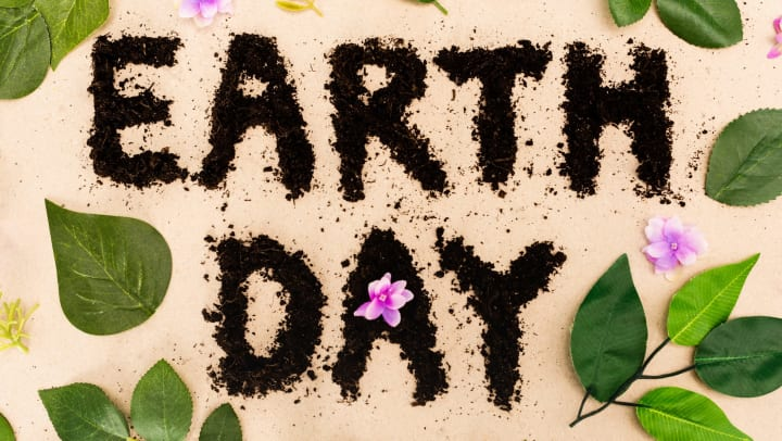 Top view of Earth Day lettering with leaves and buds on beige background.