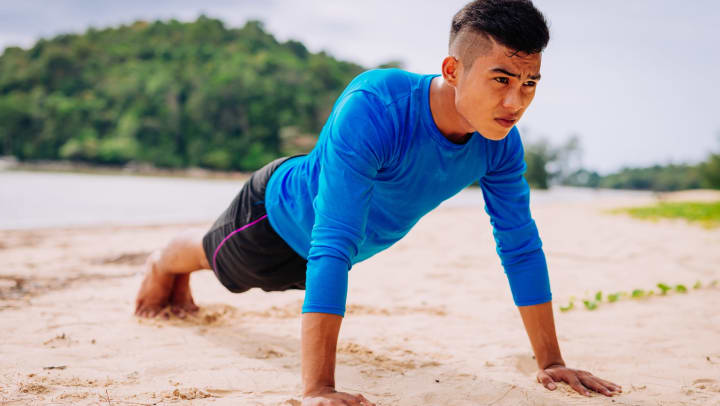 Young man in black shorts and blue long-sleeve shirt holding a plank pose on a sandy beach
