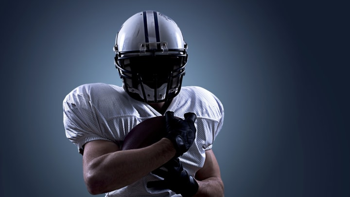 A football player in a white helmet and jersey, face covered in shadow, holding a football.