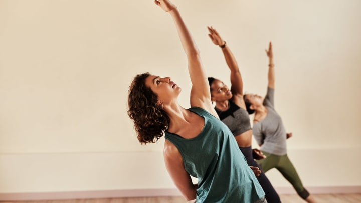 Three people doing yoga in a studio