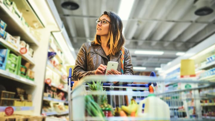 Woman with cart in grocery aisle consulting shopping list on her cell phone