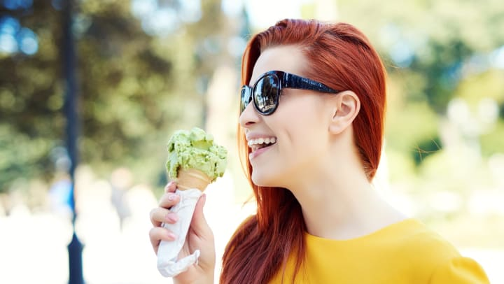 Woman in a yellow shirt and sunglasses holding a cone with a scoop of green ice cream and smiling.