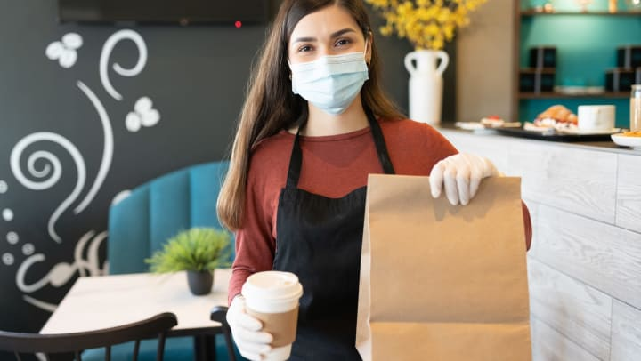 Woman wearing apron, mask, and rubber gloves, holding out paper bag and to-go coffee cup.