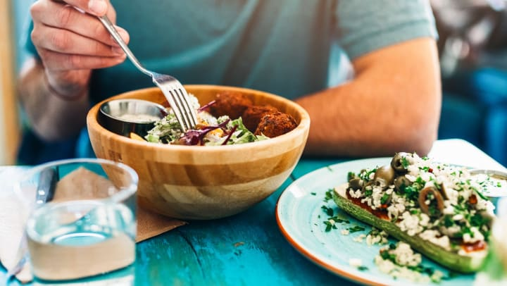 Shot of a young man eating fresh vegan salad with chickpeas balls and sesame sauce on a rustic wooden table.