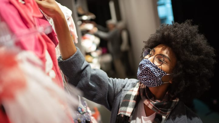 Woman wearing a mask, shopping for clothes.