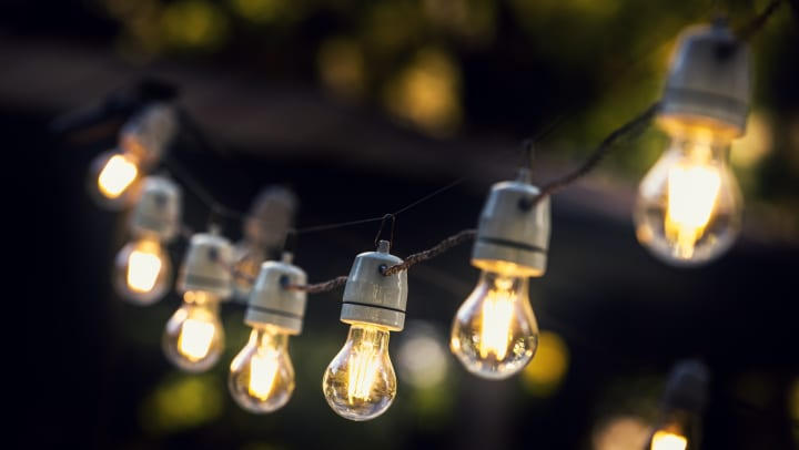 A string of bulb lights illuminating a dark outdoor space.