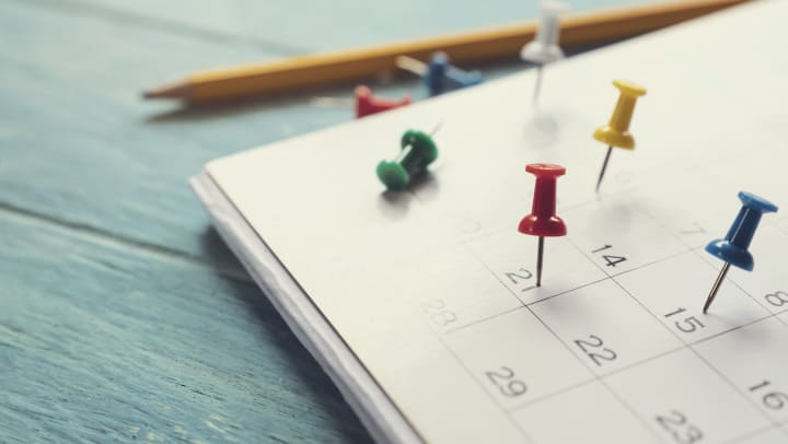 Calendar lying on a wooden surface with multi-colored push pins stuck to different dates and a pencil next to it.