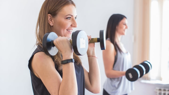 Two young women smiling and lifting dumbbells in a sunlit interior.
