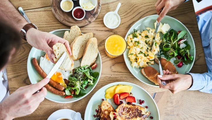 Overhead shot of two people eating breakfast at a restaurant.